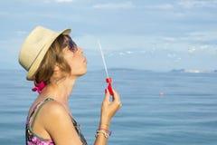 Пузыри мыла девушки дуя на пляже соломой моря нося Стоковая Фотография RF