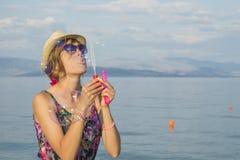 Пузыри мыла девушки дуя на пляже соломой моря нося Стоковые Фото