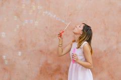 Пузыри мыла девушки дуя против красочного фона Стоковые Изображения RF