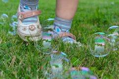 Пузыри мыла и ноги ребенка стоковые изображения