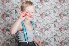 Пузыри мыла красивого радостного белокурого мальчика дуя стоковое изображение rf