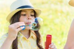Пузыри мыла милого женского ребенк дуя в природе Стоковое Фото
