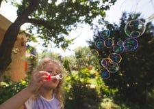 Пузыри мыла милой девушки дуя внешние на парке лета Стоковая Фотография RF
