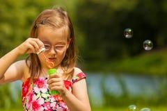Пузыри мыла ребенка маленькой девочки дуя внешние Стоковая Фотография
