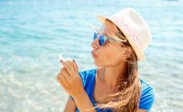 Пузыри мыла счастливой маленькой девочки дуя на seashore Стоковое Изображение