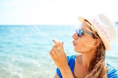 Пузыри мыла счастливой маленькой девочки дуя на seashore Стоковые Фотографии RF