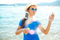 Пузыри мыла счастливой маленькой девочки дуя на seashore Стоковые Фото