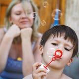 Пузыри мыла дуновения мальчика стоковые фотографии rf