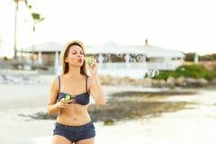 Пузыри мыла Youngwoman дуя на seashore Стоковая Фотография RF