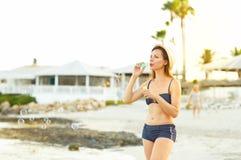 Пузыри мыла Youngwoman дуя на seashore Стоковые Фото