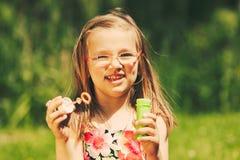 Пузыри счастливого ребенка маленькой девочки дуя внешние Стоковое Изображение
