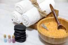 Пузыри с пестротканым солью, мягкими полотенцами, горячими камнями и солью для принятия ванны в деревянном шаре с ложкой составля Стоковые Фото