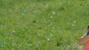 Пузыри дуновения мамы и дочери Семья в парке Дети с мамой играют с пузырями акции видеоматериалы