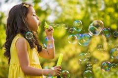 Пузырь мыла маленькой девочки дуя Стоковая Фотография RF