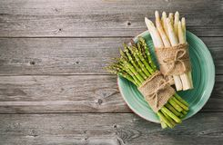 Пуки свежей зеленой и белой спаржи на деревянной предпосылке Стоковое Фото