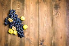 Пуки свежих зрелых виноградин и смокв на предпосылке деревянной предпосылки красивой с ветвью виноградин Темные смоквы виноградин Стоковое Изображение RF