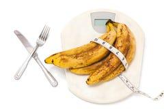 Пук бананов лежа на масштабах пола на белой предпосылке Стоковое Фото
