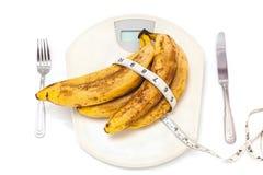 Пук бананов лежа на масштабах пола на белой предпосылке Стоковая Фотография