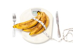 Пук бананов лежа на масштабах пола на белой предпосылке Стоковые Изображения RF