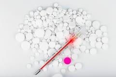 Пук белых таблеток с термометром разбросанные пилюльки Стоковое Изображение RF