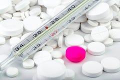 Пук белых таблеток с термометром разбросанные пилюльки Стоковые Изображения RF