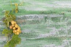 Пук больших зеленых желтых виноградин на старой grren треснутая покрашенная деревянная предпосылка Стоковые Фото