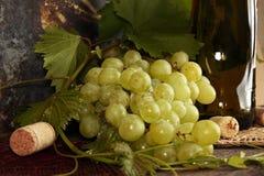 Пук виноградины зеленый с листьями против бутылки вина предпосылки Стоковое Изображение