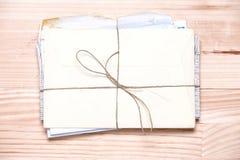 Пук винтажных писем на светлой деревянной предпосылке Аннотация стоковое фото