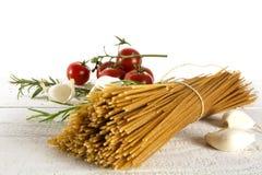 Пук всех макаронных изделий спагетти пшеницы на белой древесине с некоторым Tom Стоковые Изображения RF