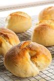 Пук всех, свежих испеченных плюшек пшеницы на охладительной решетке на белизне Стоковое фото RF