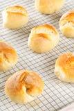 Пук всех, свежих испеченных плюшек пшеницы на охладительной решетке на белизне Стоковые Фото