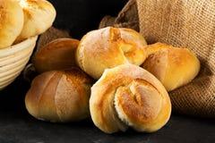 Пук всех, свежих испеченных плюшек пшеницы на темном деревянном столе Стоковые Фотографии RF