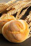 Пук всех, свежих испеченных плюшек пшеницы с ушами пшеницы на темном w Стоковые Изображения