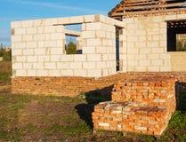 Пук выровнянный вверх использовал кирпичи на паллете на заходе солнца, доме под конструкцией на предпосылке стоковая фотография