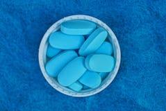 Пук голубых таблеток в белой крышке бутылки на шерстяной ткани стоковое изображение