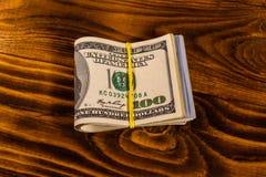 Пук 100 долларовых банкнот с резиной на деревянном tabl Стоковая Фотография RF