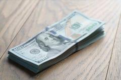 Пук долларов на таблице древесины дуба Стоковая Фотография RF