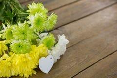 Пук желтых цветков с биркой формы сердца на деревянной планке Стоковые Изображения RF