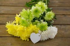 Пук желтых цветков с биркой формы сердца на деревянной планке Стоковое Изображение