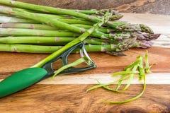 Пук зеленой спаржи с peeler на деревянной предпосылке Стоковые Фотографии RF