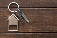 Пук ключей с домом сформировал keychain на коричневой древесине Стоковые Фото
