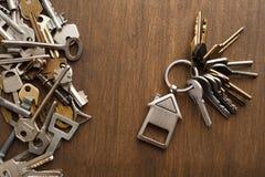 Пук ключей с trinklet дома на деревянном столе Стоковое Фото