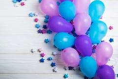 Пук красочных воздушных шаров партии с бумажными звездами на белой деревянной предпосылке стоковые изображения
