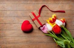 Пук красочных тюльпанов, подарка и сердца сформировал игрушку на wonde Стоковое фото RF