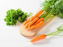 Пук морковей и пук петрушки на разделочной доске на белой таблице Стоковые Изображения RF