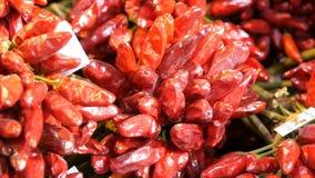 Пук накаленных докрасна перцев chili на счетчике рынка сток-видео