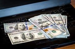Пук долларовых банкнот брошенных на клавиатуру компьтер-книжки отличал defocused bokeh Стоковое фото RF