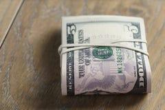 Пук долларов на таблице древесины дуба Стоковые Изображения