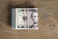 Пук долларов на таблице древесины дуба Стоковые Фотографии RF