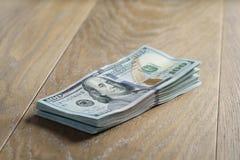 Пук долларов на таблице древесины дуба Стоковые Фото
